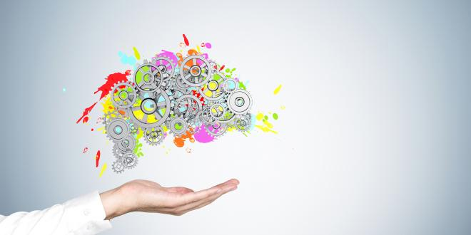 A man's hand in a white shirt holding a colored brain shape and gears on top. Concept of brain support.